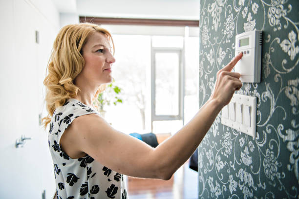 Smiling Woman Adjusting Thermostat On Home Heating System stock photo