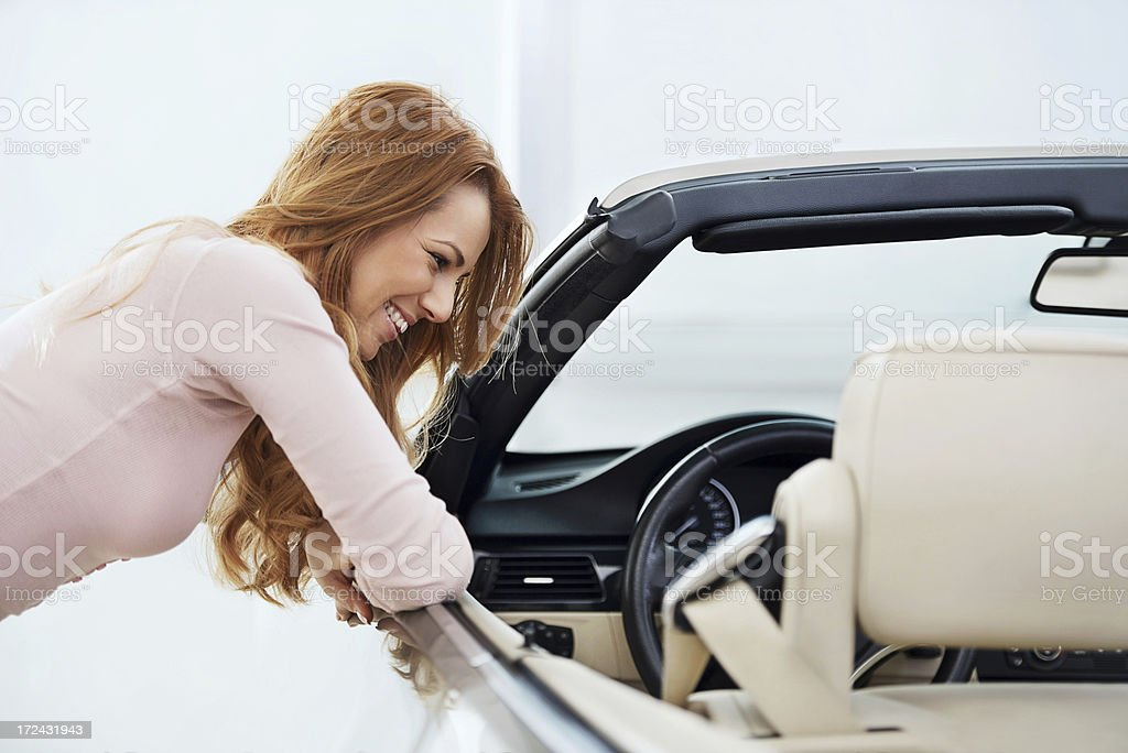 Smiling woman admires the new convertible car royalty-free stock photo