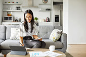 istock Smiling woman analyzing documents at home 1211318693