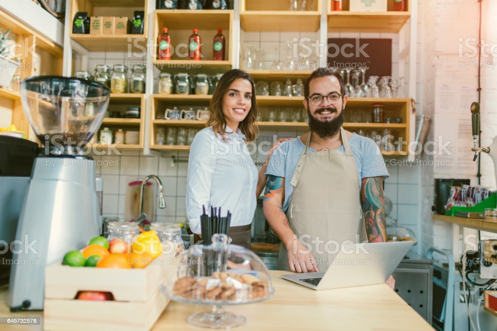 Smiling Woman and Bearded Man Working In  Smoothie Cafe stock photo