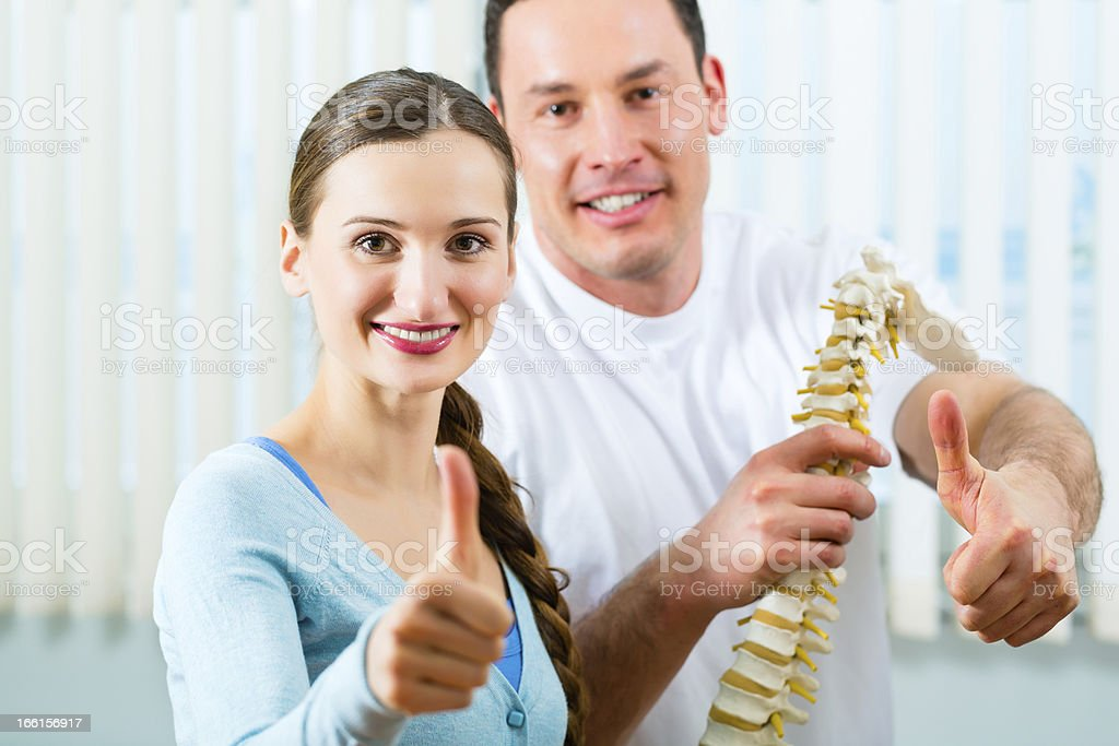Smiling woman and Doctor holding a model of a spine royalty-free stock photo