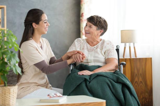 lächelnde frau und glückliche großmutter - altenpfleger stock-fotos und bilder