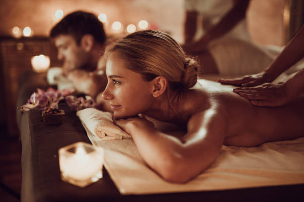 smiling woman and her boyfriend having back massage at the spa. - massaggio foto e immagini stock