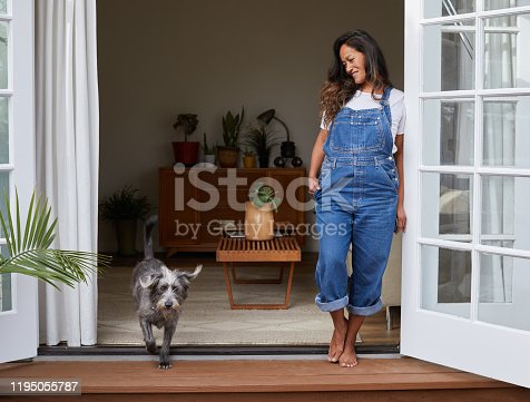 Smiling mature woman standing on her living room patio with her dog in the morning