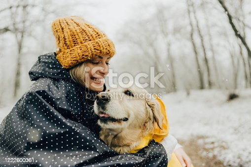 Photo of smiling woman and her dog in a snowy day