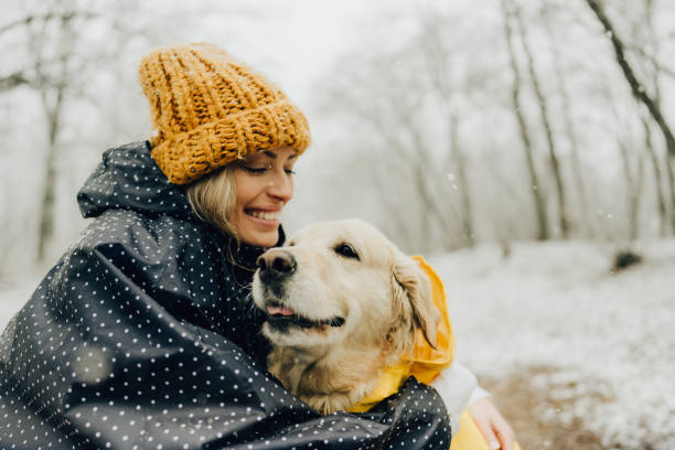 Smiling woman and her dog in a snowy day stock photo