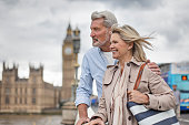 Smiling man and woman looking away while standing on Westminster Bridge. Mature couple is against Big Ben. They are wearing casuals.