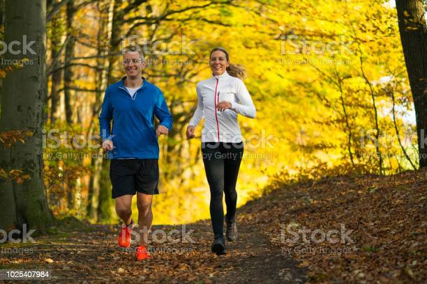 Photo of smiling woman and man jogging together through forest in autumn