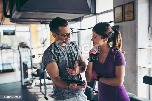 860045834istockphoto Smiling woman and personal trainer making exercise plan in gym 1058409562
