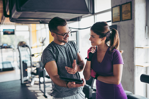 860045834 istock photo Smiling woman and personal trainer making exercise plan in gym 1058409562