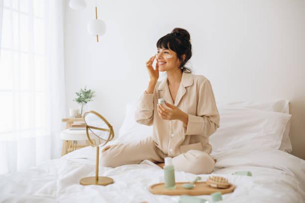 mujer sonriente aplicando crema facial sentada en la cama - skin care fotografías e imágenes de stock