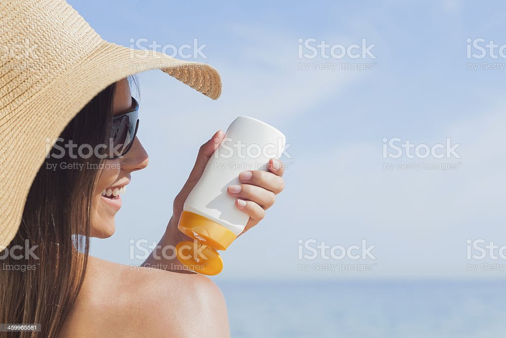 Smiling woman applying sunscreen on her shoulder stock photo