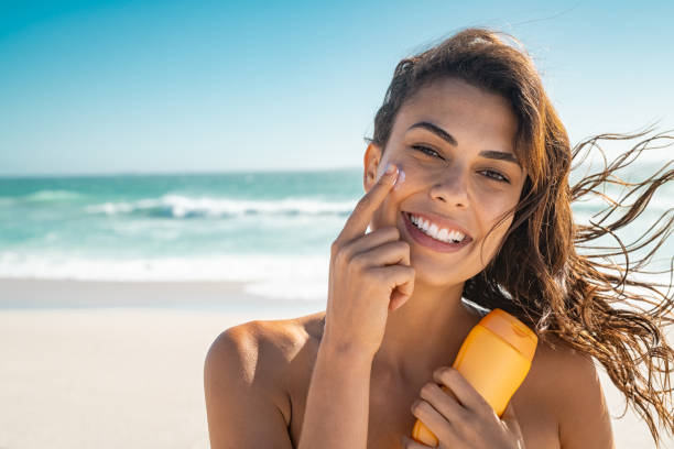 Smiling woman applying sunscreen stock photo