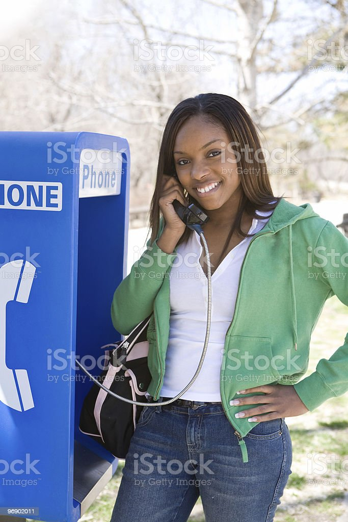 Smiling Woman at a Pay Phone royalty-free stock photo