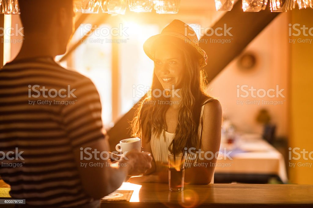 Smiling woman at bar counter ordering a cup of coffee. zbiór zdjęć royalty-free