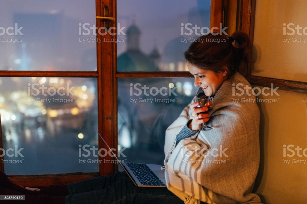 Smiling woman at home watching movie on the laptop stock photo
