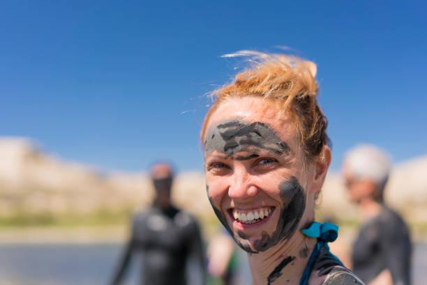 Lächelnde Frau am Issyk-Kul Salty Lake mit Schlamm über dem Gesicht, Kirgisistan – Foto