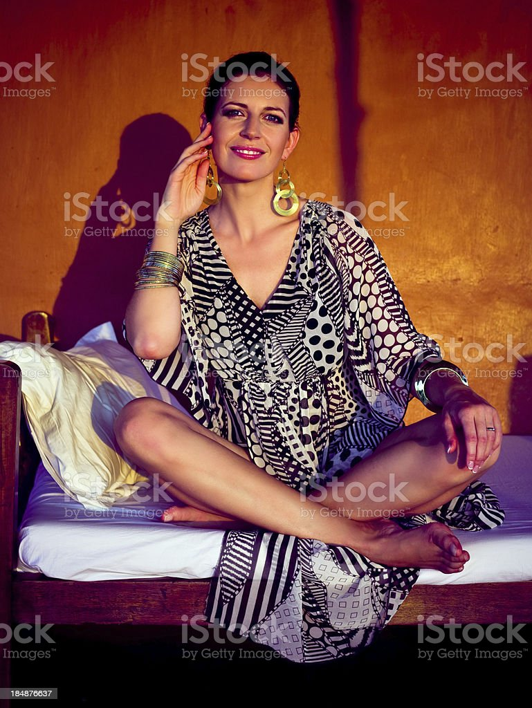 Smiling woman at sunset Beautiful woman wearing summer dress and gold jewelry sitting cross-legged on a bed on veranda at sunset, looking at camera and smiling. 30-34 Years Stock Photo