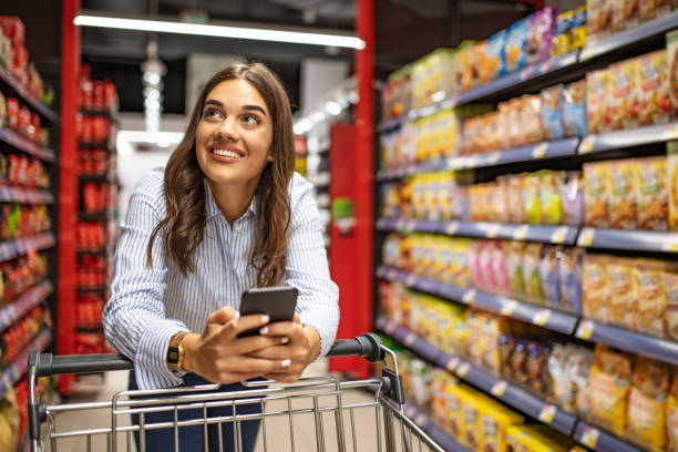 Smiling woman at supermarket. Smiling woman at supermarket. Happy woman at supermarket. Beautiful young woman shopping in a grocery store/supermarket. Shopping lists in app format supermarket stock pictures, royalty-free photos & images
