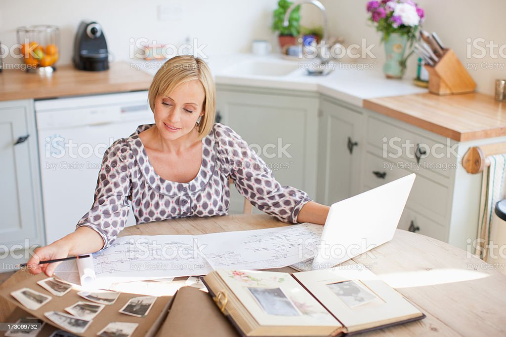 Smiling woman at table with old photographs and genealogical tree stock photo