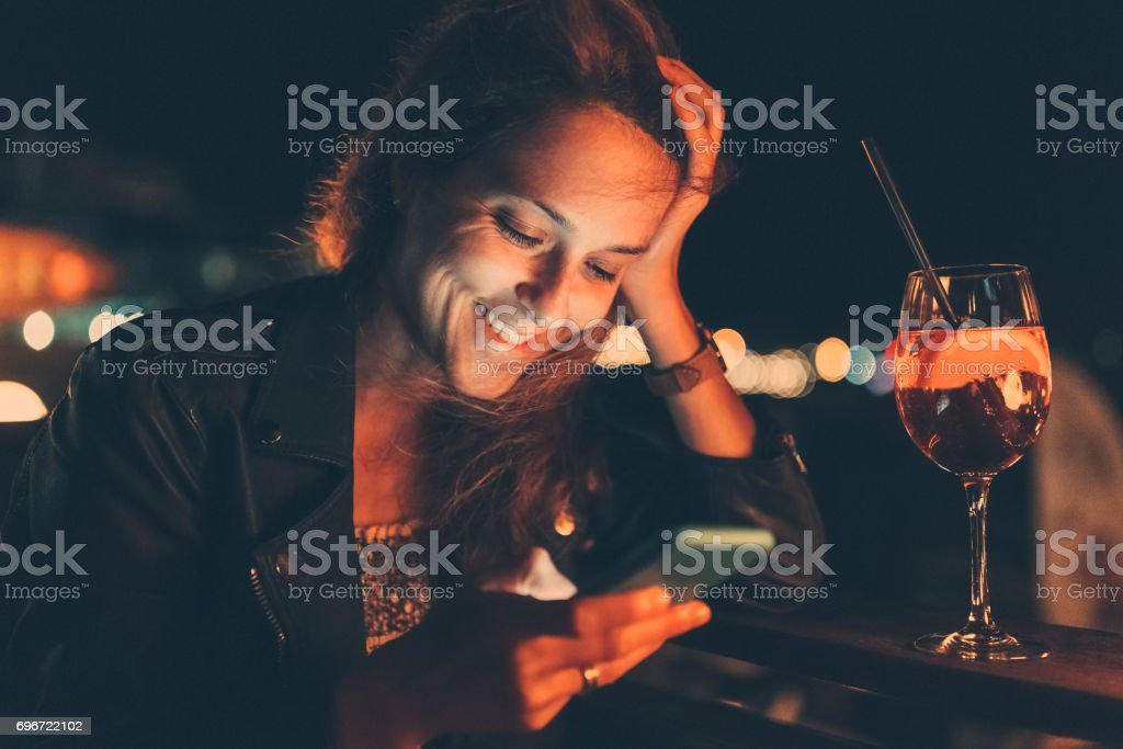 Smiling woman at the beach bar texting stock photo