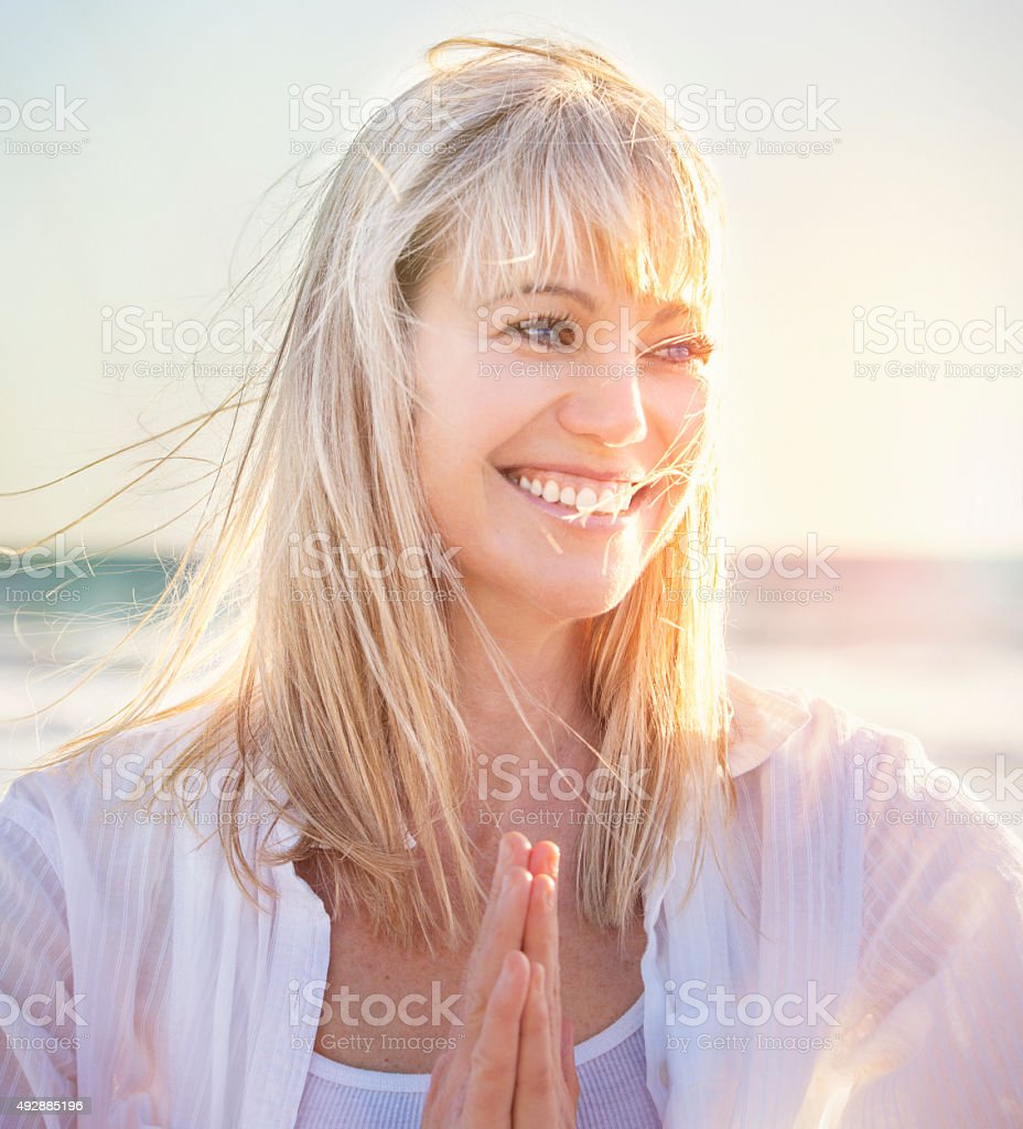 smiling woman at the beach doing yoga stock photo