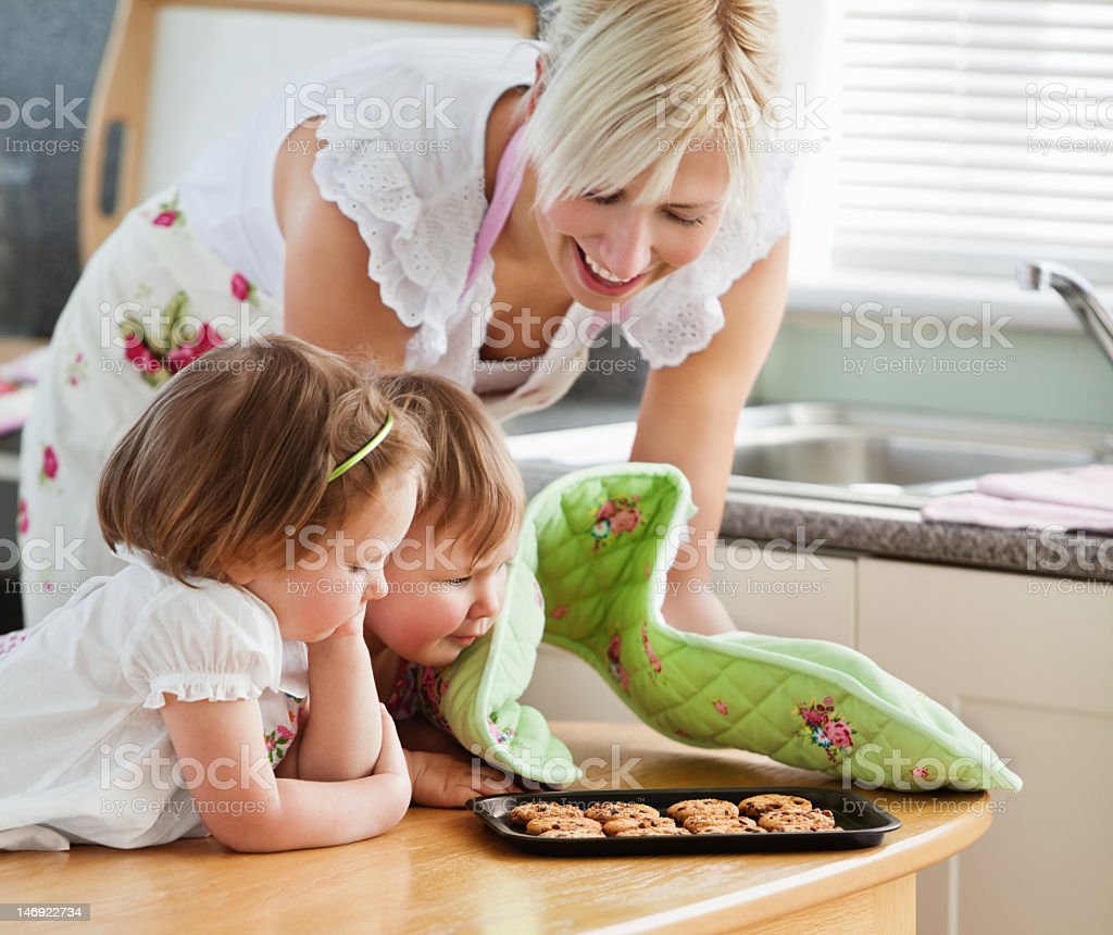 Smiling woman baking cookies with her daughters royalty-free stock photo