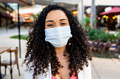 Smiling woman behind face protection mask - coronavirus / covid-19
