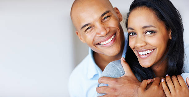 Smiling woman being embraced by her boyfriend stock photo
