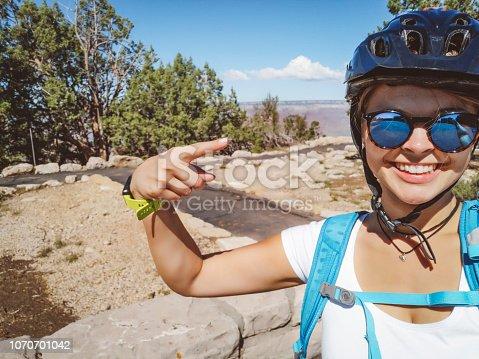 807387518 istock photo Smiling woman biker exploring the Grand Canyon 1070701042