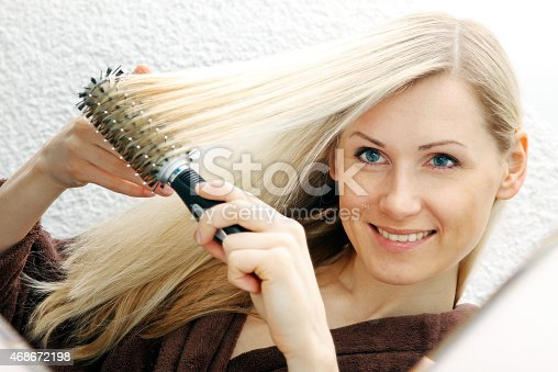 886414246istockphoto smiling woman brushing her long blond hair 468672198