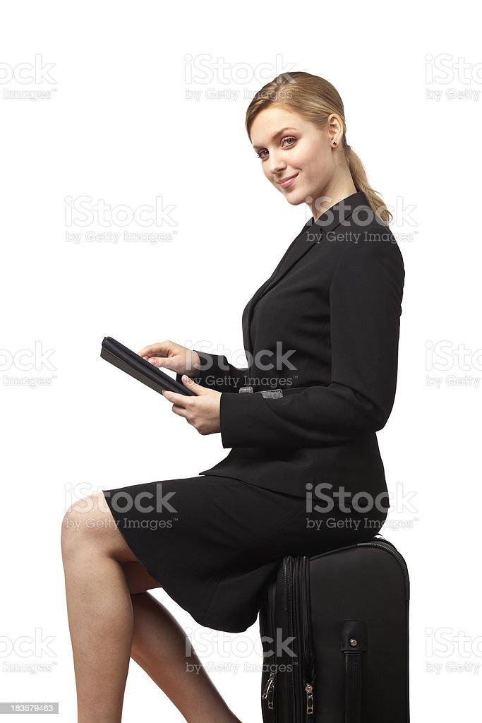 Smiling Woman Business Traveler Sitting on Luggage Using Tablet Computer stock photo