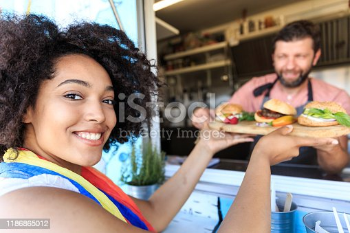 istock Smiling woman buying burgers and sandwiches from food truck 1186865012