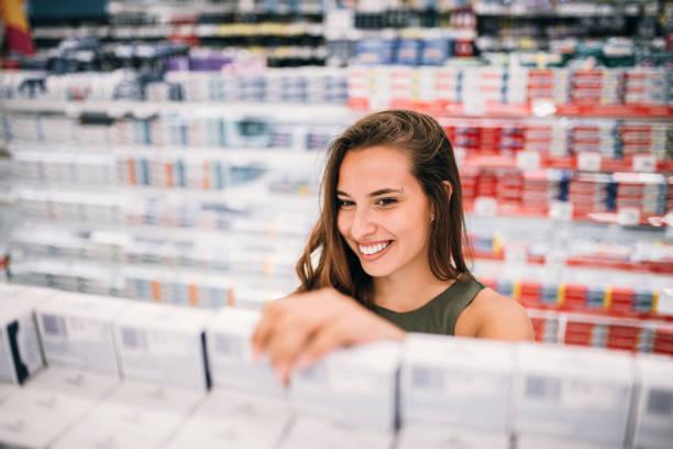 lächelnde frau in apotheke kosmetik kaufen. - drogerie stock-fotos und bilder