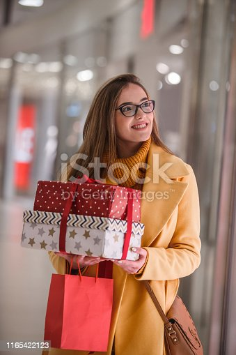 518885222istockphoto Smiling woman buying presents 1165422123