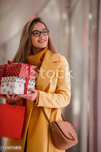518885222istockphoto Smiling woman buying presents 1174711875