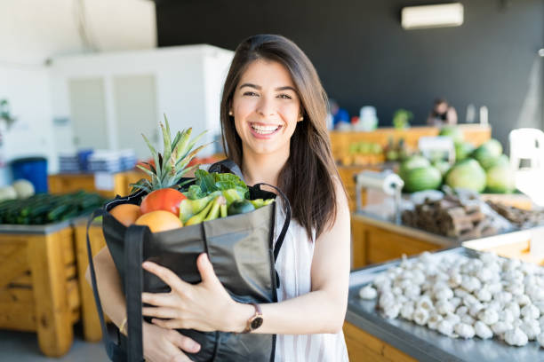Smiling Woman Carrying Fresh Healthy Food In Shop stock photo