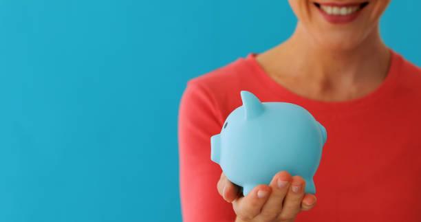 Smiling woman carrying piggy bank stock photo