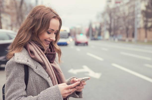 gülümseyen kadın bir otobüs beklerken cep telefonu üzerinden e-posta kontrol - sefer tarifesi stok fotoğraflar ve resimler