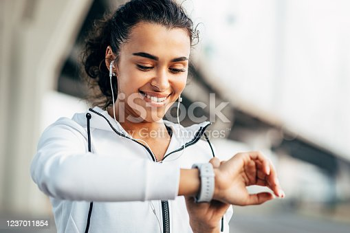 istock Smiling woman checking her physical activity on smartwatch. Young female athlete looking on activity tracker during training. 1237011854