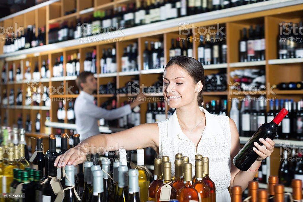 Smiling woman choosing bottle in wine shop - foto de acervo
