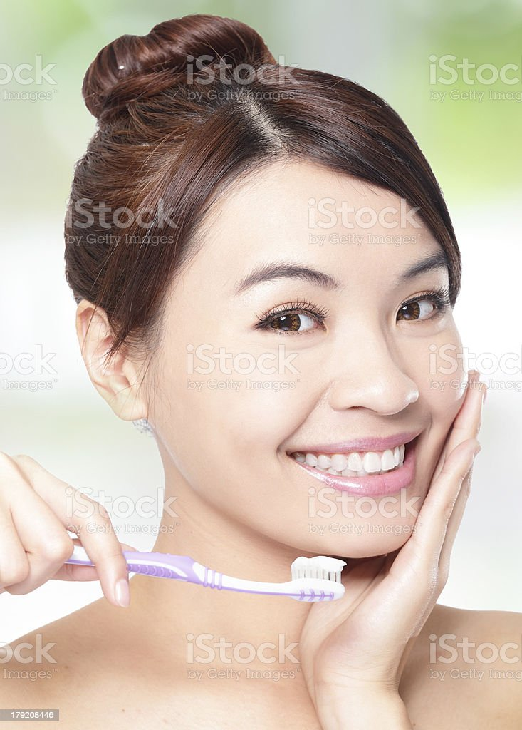 smiling woman cleaning teeth with toothbrush royalty-free stock photo