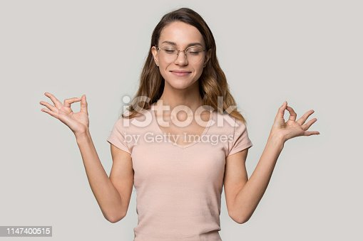 Smiling beautiful millennial woman wearing glasses peach color t-shirt meditating in studio do yoga exercise over grey wall, girl closed eyes feels harmony make fingers mudra gesture no stress concept