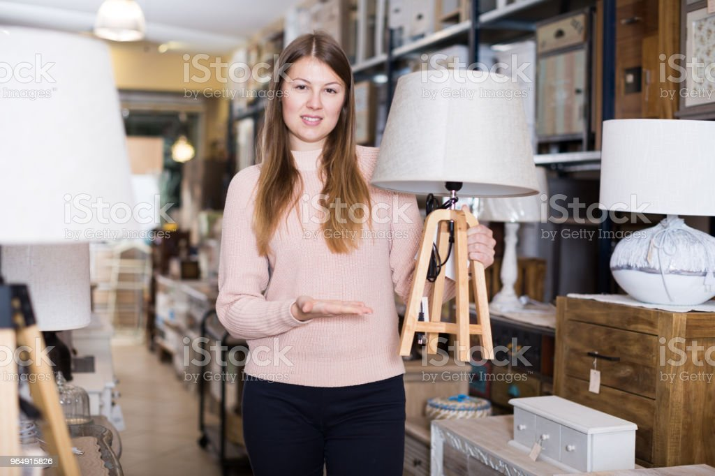 Smiling woman consumer choosing torchere royalty-free stock photo