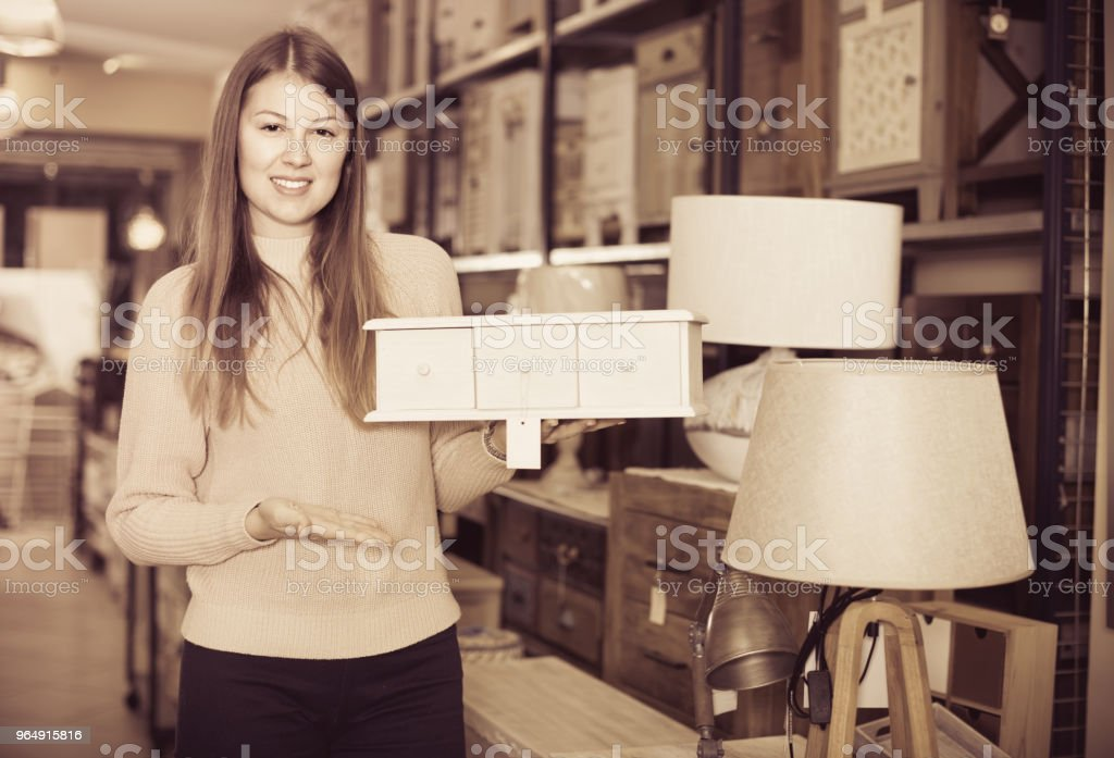 Smiling woman consumer choosing wooden box in furniture shop royalty-free stock photo
