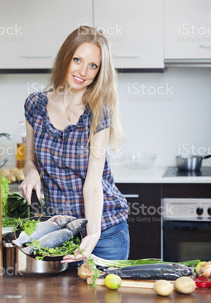 Smiling woman cooking lubina  in skillet royalty-free stock photo