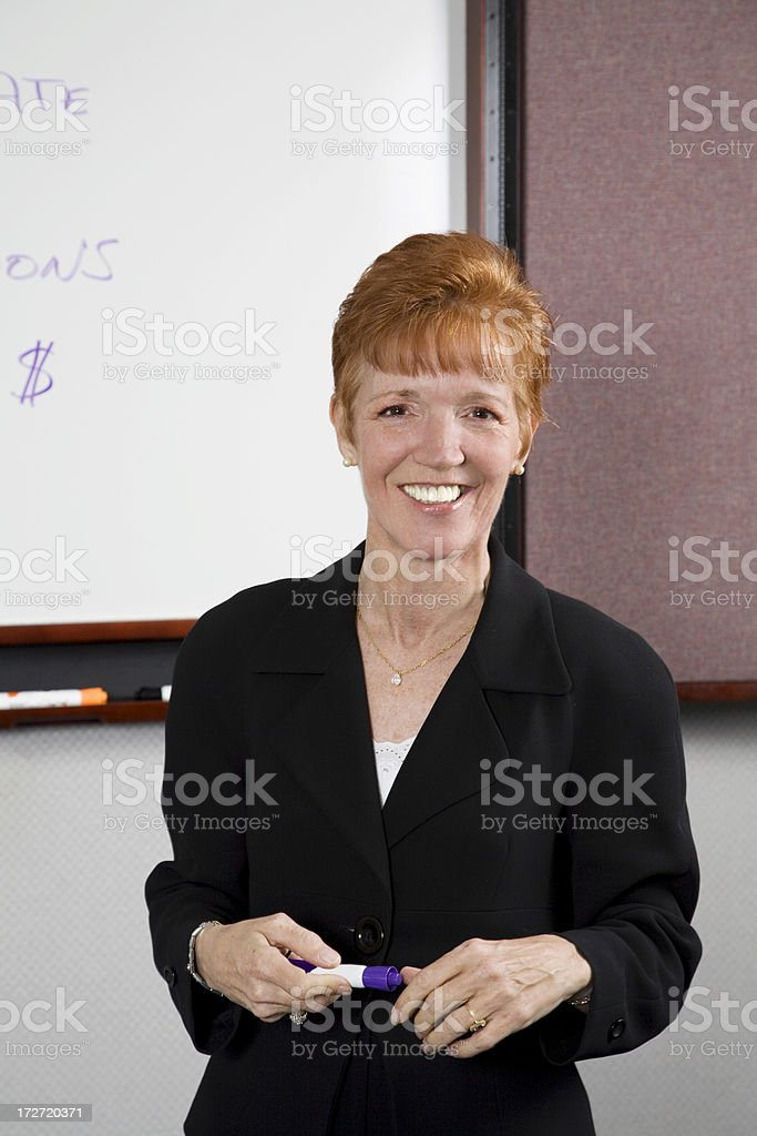 Smiling Woman Corporate Trainer in front of Whiteboard royalty-free stock photo