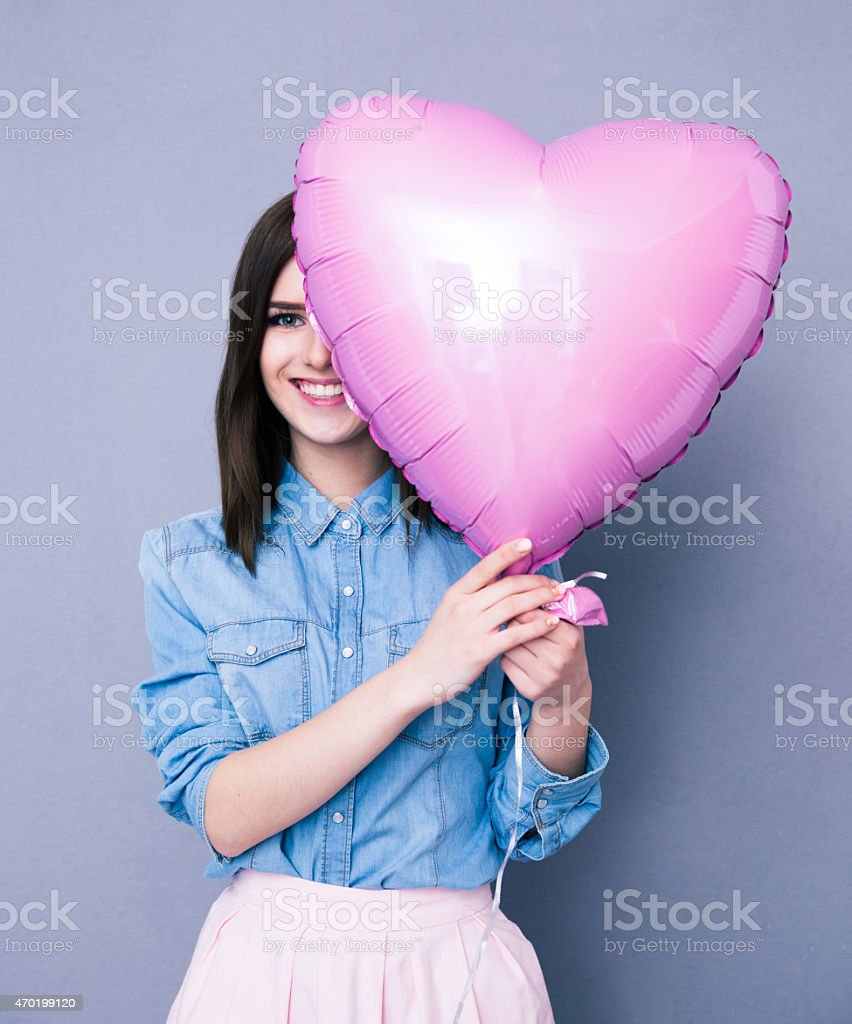 Smiling woman covering her eye with heart shaped balloon stock photo