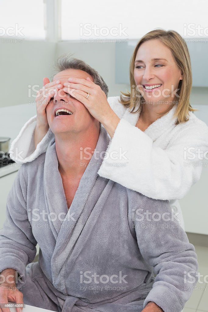 Smiling woman covering mans eyes in kitchen stock photo