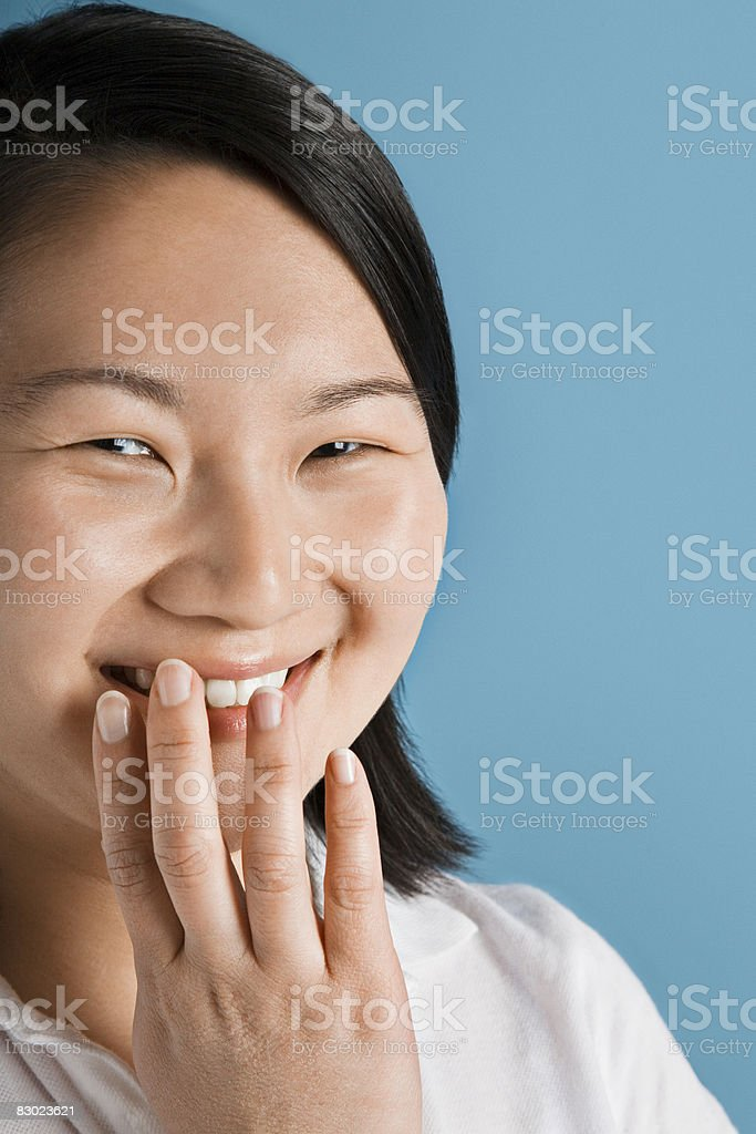 Smiling woman covering mouth with hand royaltyfri bildbanksbilder